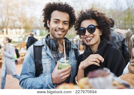 Portrait Of Happy Cute Dark-skinned Couple With Afro Hairstyle, Strolling On Food Festival, Tasting