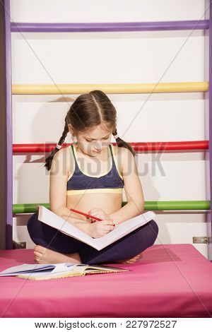 Little Caucasian 6-8 Years Old Girl Doing One's Lessons At The Gym