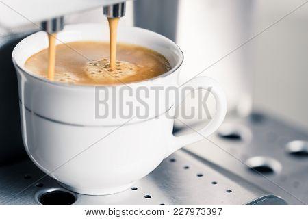 Creamy Coffee Pouring Into A Cup, Closeup, Copy Space