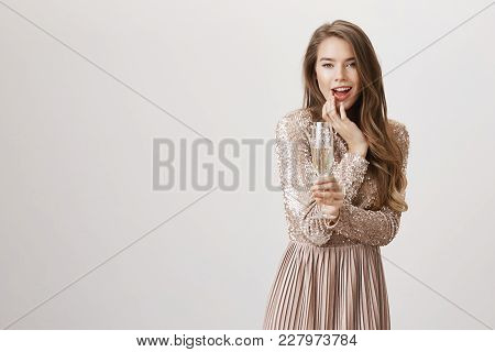 Seducing European Female Sensually Touching Lip While Smiling And Flirting, Holding Glass With Champ