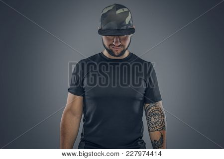 Bearded Male In A Baseball Cap Looking Down On A Grey Background.