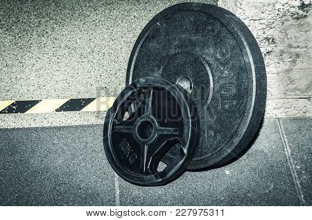Two Heavy Black Weight Plates On The Gym Floor Ready For Fitness Workout