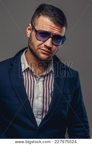 Portrait Of Bearded Man In A Suit And Sunglasses Isolated On Grey Background.