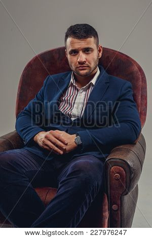 Serious Bearded Man In A Suit Sits On A Chair.