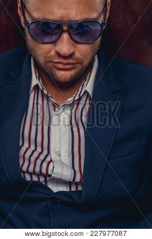 Serious Bearded Man In A Suit And Sunglasses Sits On A Chair.