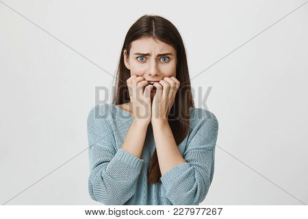 Studio Portrait Of Horrified And Shocked Girl Holding Hands Near Mouth And Looking Afraid At Camera,