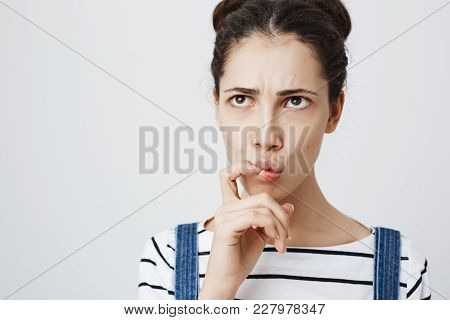 Close-up Portrait Of Worried Young European Female, Frowning And Folding Lips While Thinking About S