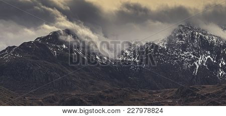 Panoramic View Of Mountain Range Capped In Dramatic Clouds At Winter. Snowdonia National Park In Nor