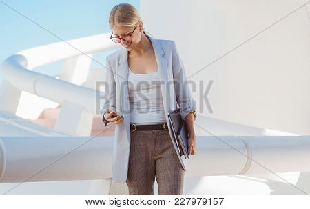 Young Blond Businesswoman Posing In A Modern Building Checking Her Phone.