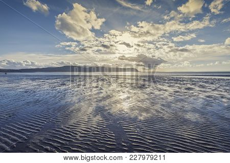Bright Dramatic Clouds Over Sandy Beach At Low Tide. Llandudno In North Wales. Uk