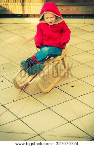 Childhood, Kids Imagination Concept. Dissatisfied Little Young Boy Playing Outside On Sled But There