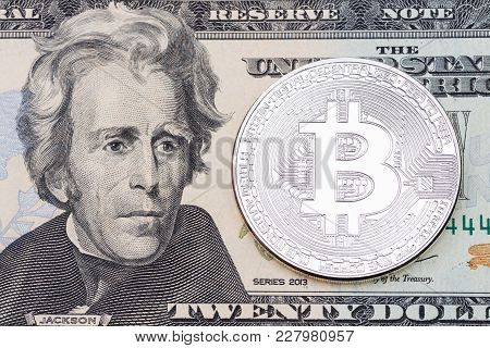 Silver Bitcoin On Twenty Dollas Banknote. High Resolution Photo.