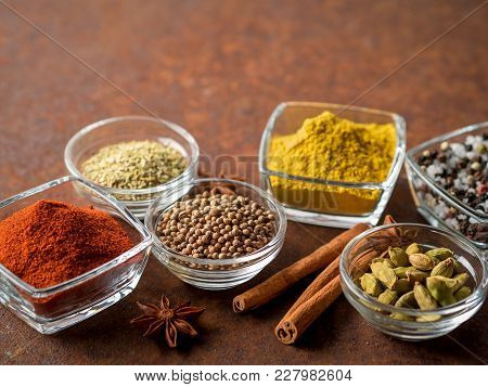Set Of Spices On A Dark Brown Rusty Metal Table - Coriander Seeds, Ground Red Pepper, Salt, Black Pe