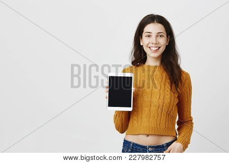 Advertisement And Human Face Expressions Concept. Young Attractive Woman Holding Tablet To Show It A