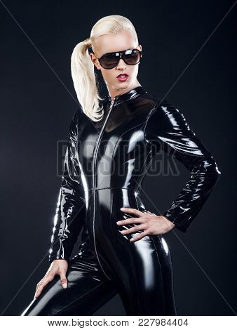 Sexy Blond Female In Sunglasses And In Latex Black Costume Isolated On Dark Background.