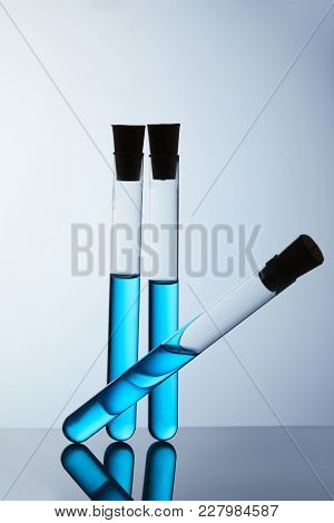 Composition Of Test Tubes Filled With Blue Liquid On Grey