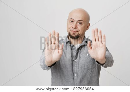 Body Language. Disgusted Serious Angry Bald Man With Beard In Grey Shirt Posing Against Studio Wall,