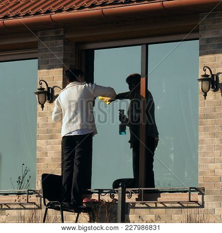 Woman Washes Window In The Spring In The Sun