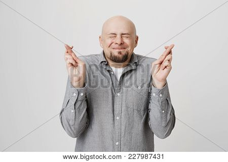 Portrait Of Happy Hopeful Bearded Handsome Man Making Wish Crossing His Fingers Over White Backgroun