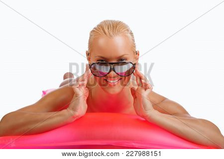 Sexual Blond Woman In Sunglasses Lying In A Pink Water Matress.