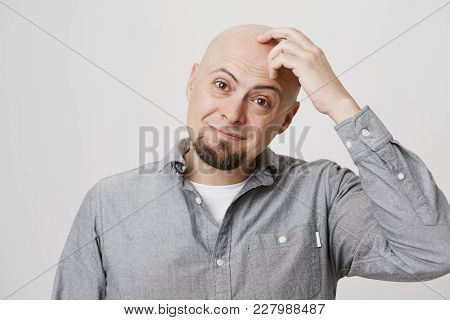 Close-up Portrait Of Charming Bald Caucasian Guy Touching His Head While Frowning And Smiling, Recal