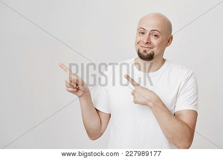 Portrait Of Satisfied Attractive Bald Caucasian Man In White T-shirt Smiling And Pointing Left With