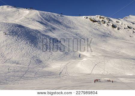 Steep Gradient Piste In Italian Alps Against A Beautiful Blue Sky