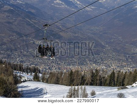 Four Middle Aged Men Skiers Take A Chair Lift Up The Mountain At Pila Ski Resort In Aosta Valley, It