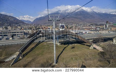Gondola Cable Car To Ski Resort Of Pila. Looking Towards Valley At Town Of Aosta Before Crossing A M