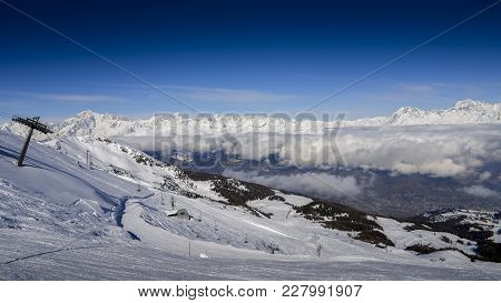 Chairlift At Italian Ski Area Of Pila On Snow Covered Alps And Pine Trees During The Winter With Mt.