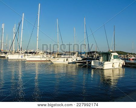 Boating Lifestyle. Boats Docked In A Marina With A Rocky Foreground And The Beginning Of A Sunset In