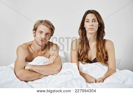 Unsatisfied Disappointed Couple Sitting In Bed Under Blanket, Looking At Camera, Boyfriend Crosses H
