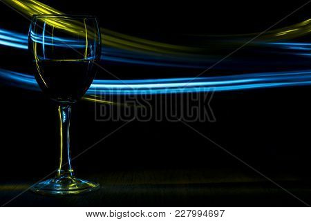 A Glass Of Red Wine In Night Club. Yellow And Blue Blurred Bands. The Light Effect.