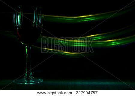 A Glass Of Red Wine In Night Club. Green And Yellow Blurred Bands. The Light Effect.