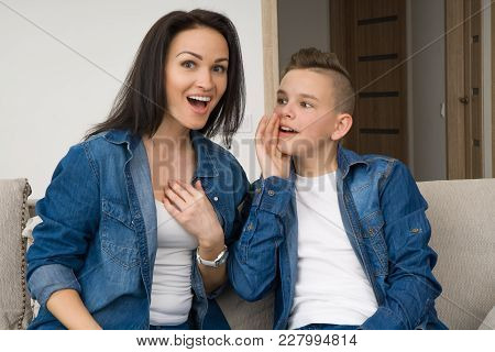 Mother And Child Gossiping. Family Talking. Portrait Of Mother And Her Son Sitting On Sofa At Home,