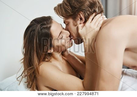 Young Hot Girlfriend Kissing Attractive Guy And Holding Hands On His Neck While Lying In Bed In Midd