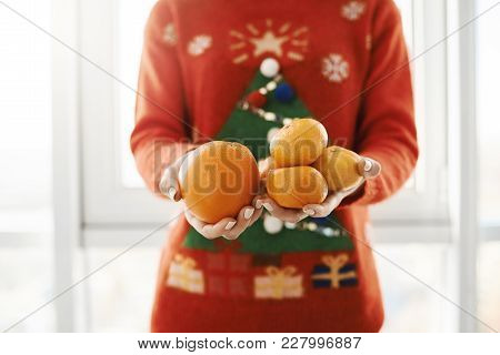 New Year And Winter Concept. Cropped Shot Of Female In Funny Christmas Sweater Holding Orange And Ta