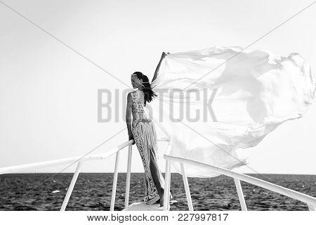Girl In Dress On Blue Sky At Ocean. Bride And Wedding Ceremony. Elegance And Fashion Model. Wedding