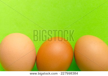 Three Brown Eggs On A Bright Light Green Background.close Up