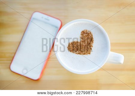 A Cup Of Coffee With A Pattern Of Cinnamon In The Form Of A Heart And In The Background A Phone With