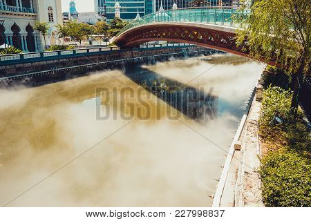 Bridge Across Gombak River. Misty Water. Kuala Lumpur Cityscape. Connection Concept. Travel To Malay