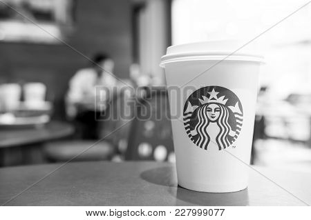 A Tall Starbucks Coffee Cup In Starbucks Offee Shop.