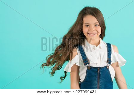 Child Smiling With Healthy Brunette Hair. Girl Smile With Flowing Long Wavy Hair On Blue Background.