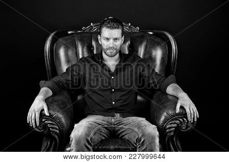 Macho Sit In Leather Armchair On Dark Background. Barber Salon, Barbershop. Fashion, Style Concept,