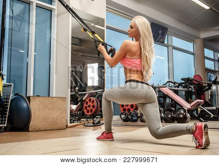 A Blond Sporty Woman Doing Exercises With Expander In A Gym.