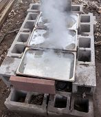 Maple sap concentrations boiling down to sweet homemade syrup in backyard evaporator system made of stainless steel pans heated over fire in cinder blocks poster