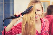 Haircare and hairstyling concept. Woman straightening her long blond hair using straightener tool. poster