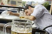 Alcohol abuse: drunk young man or student lying down on a table with beer bock still in hand focus on glass up front. poster