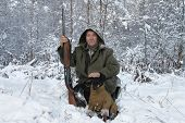 A hunter with a dog in winter forest poster