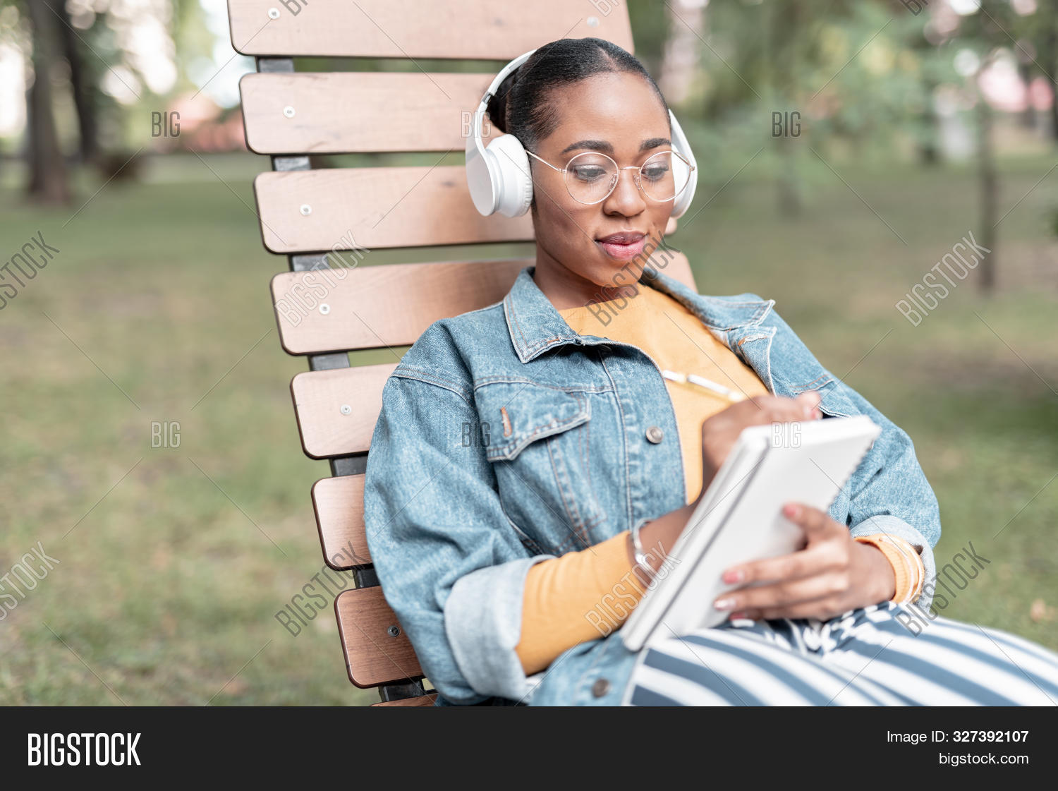 Merry Girl With Sketchbook And Earphones In Park Stock Photo
